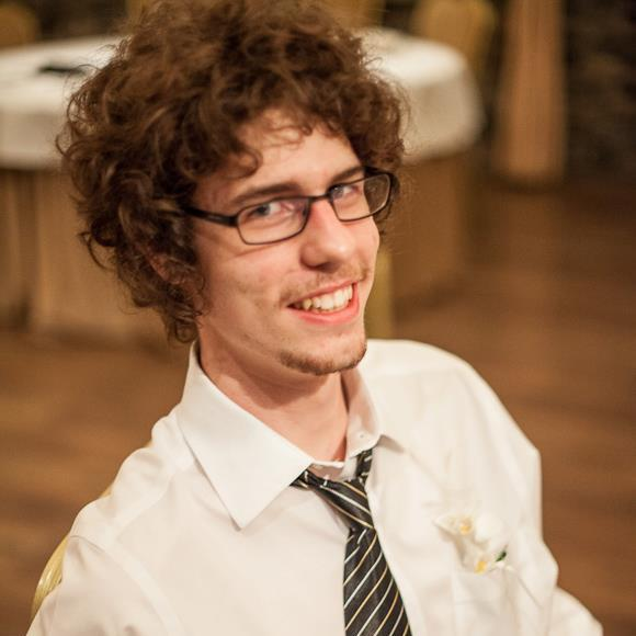 Brigham Bartol is a smiling young man with curly hair and glasses in a shirt and tie